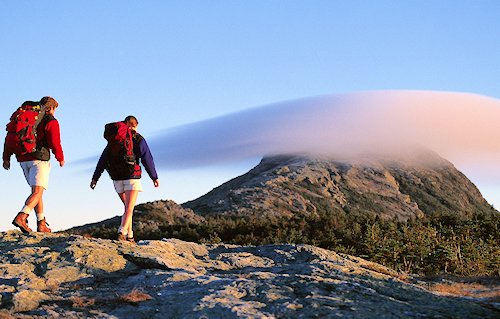Hikers approach mountain with lenticular cloud.