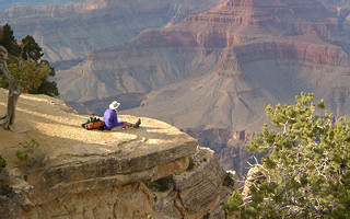 Hiker looks out over Grand Canyon